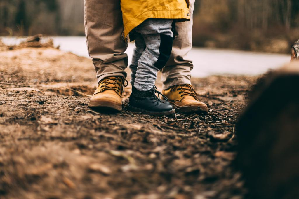 Father and son's legs pictured standing together on a dirt path, each in boots