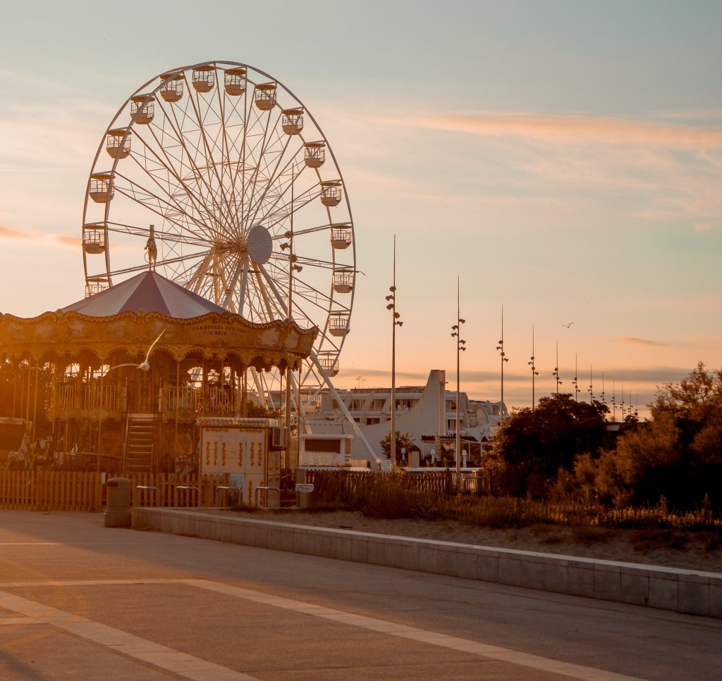 empty fair grounds at sunset with a large ferris wheel and carrousel